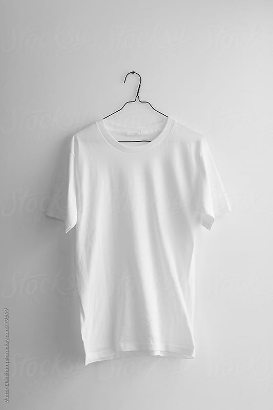 Plain white t-shirt hanging on the wall. by Victor Deschamps for Stocksy United