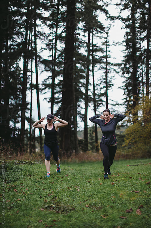 Two caucasion female friends working out together in nature by Rob and Julia Campbell for Stocksy United