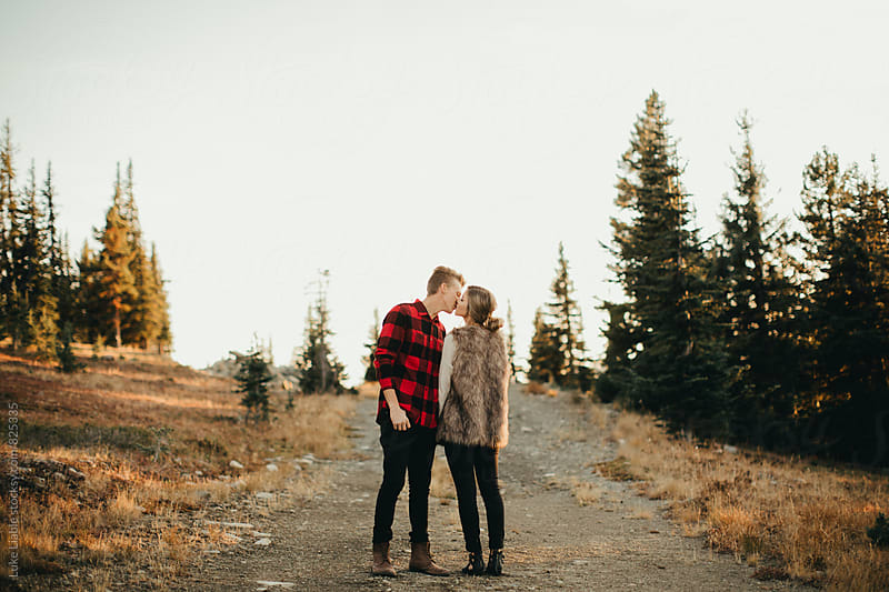 Young engaged couple exploring mountain side roads by Luke Liable for Stocksy United