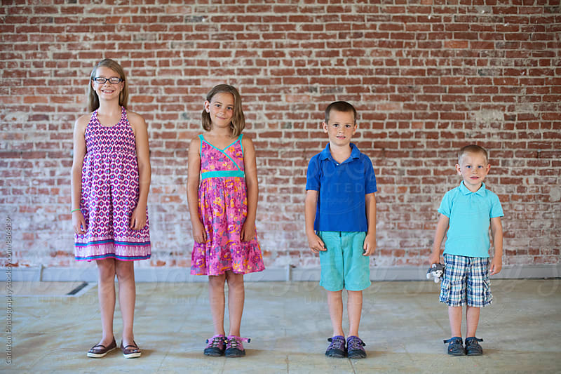 Four siblings in descending height order in an empty warehouse by Carleton Photography for Stocksy United