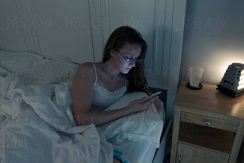 Woman Wakes up for Work and Checks Messages by suzanne clements for Stocksy United