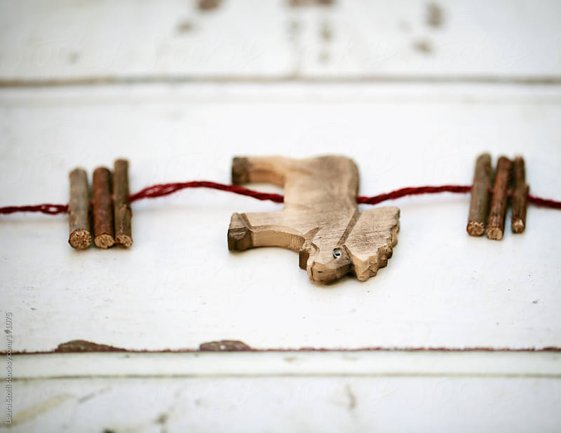 Rural decoration: close-up of reindeer shaped inlaid wood garland by Laura Stolfi for Stocksy United