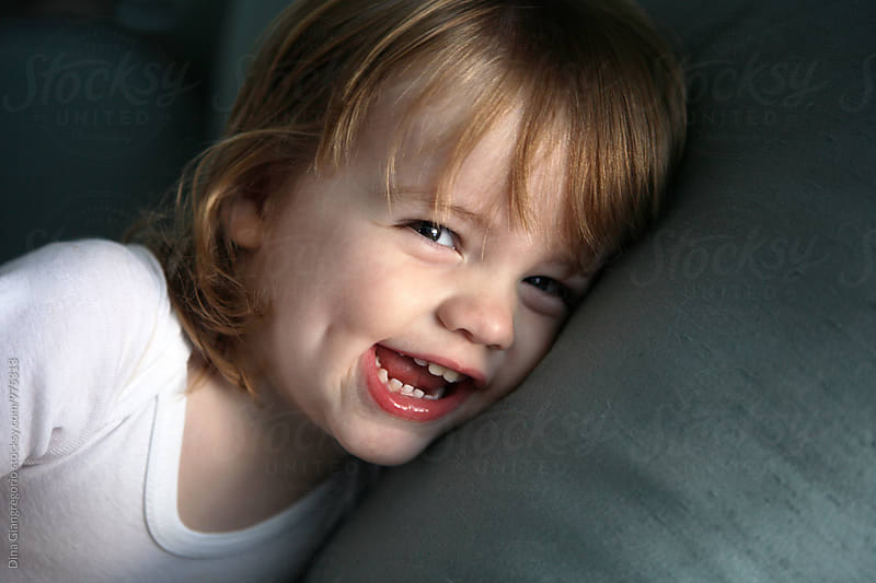 Long Haired Boy With Dimple Laughing On Pillow by Dina Giangregorio for Stocksy United