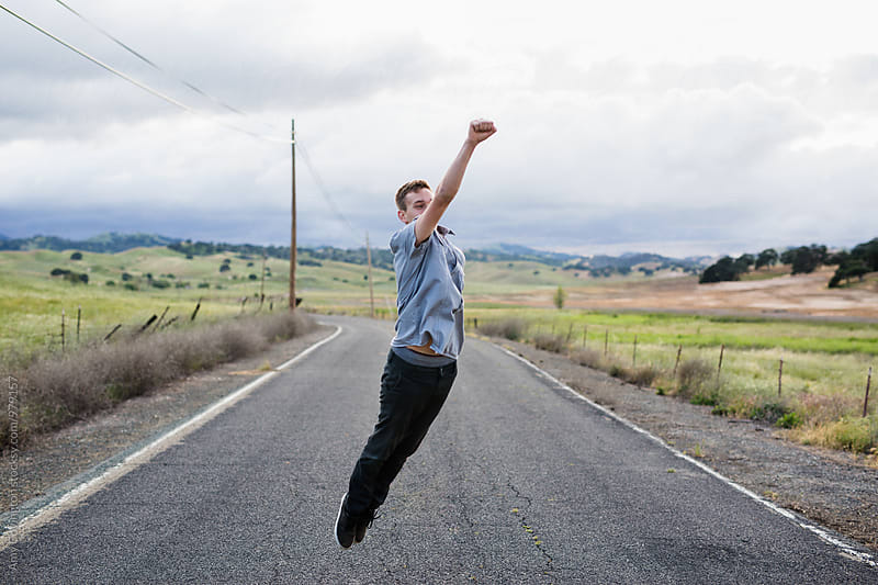 Young man jumping in the air like a super hero by Amy Covington for Stocksy United