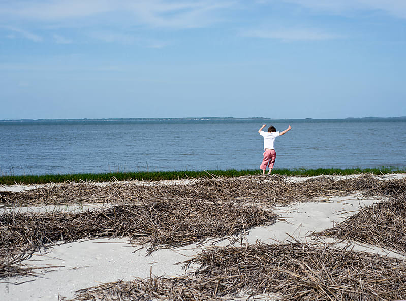 Young boy dances on a beach by Cara Dolan for Stocksy United