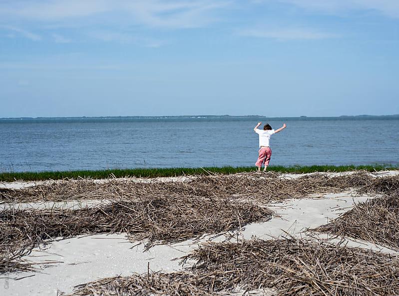 Young boy dances on a beach by Cara Slifka for Stocksy United