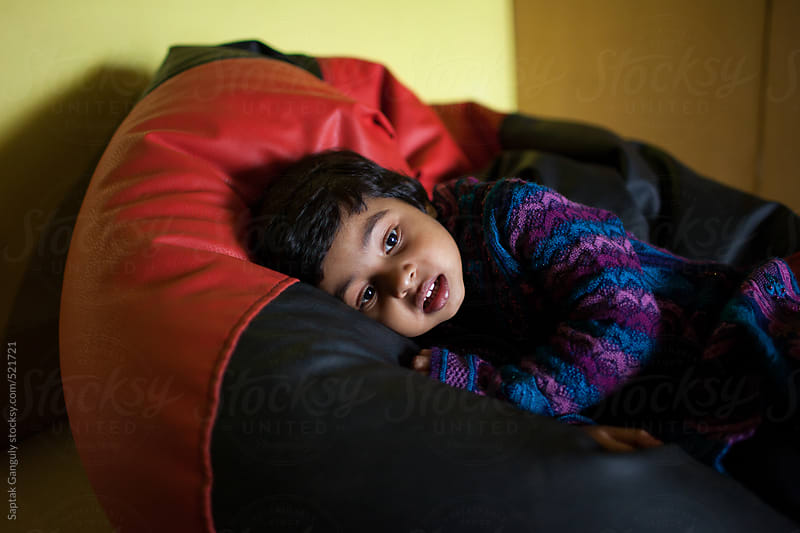 Toddler resting on a air bag sofa by Saptak Ganguly for Stocksy United