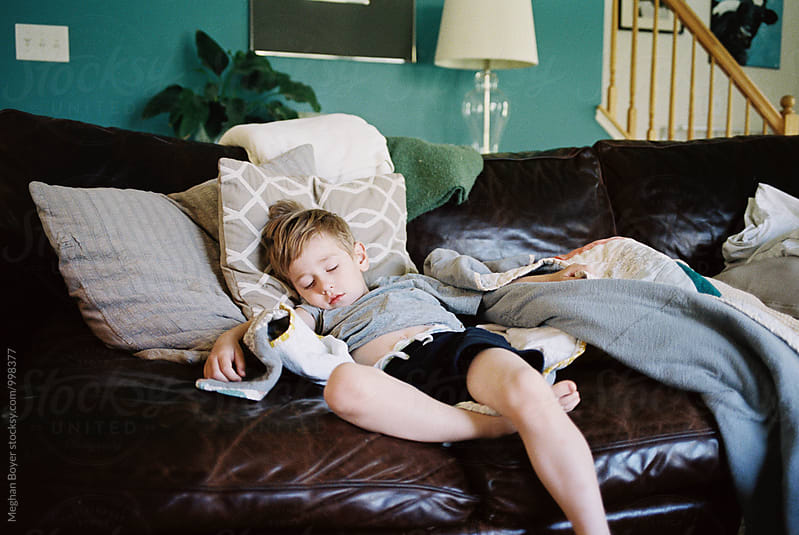 Napping Boy on a big couch by Meghan Boyer for Stocksy United