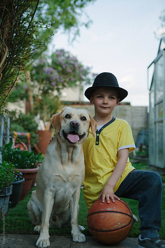 Little boy with his pet dog in his garden by kkgas for Stocksy United