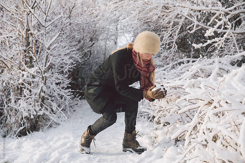 Woman making snowball in winter landscape by Lior + Lone for Stocksy United