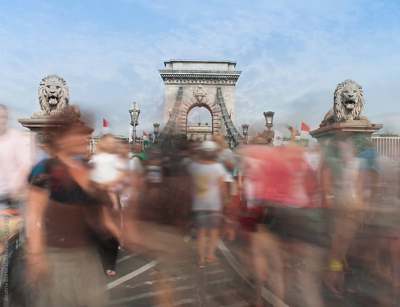 Out of focus crowd of people walking in front of Chain Bridge, Budapest by Beatrix Boros for Stocksy United