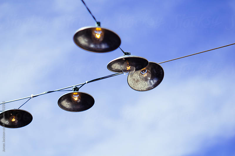 Patio lights against a blue sky with some hazy clouds. by James Jackson for Stocksy United