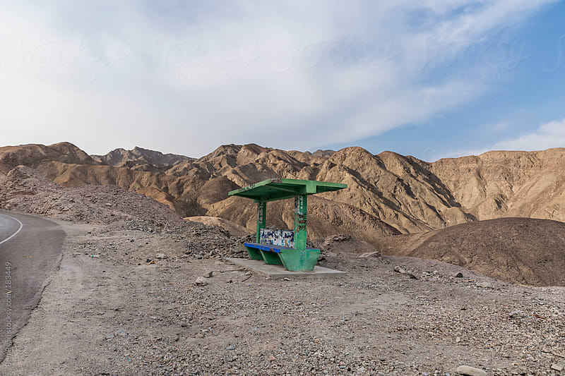 Green concrete bus stop in a desert valley by Ben Ryan for Stocksy United