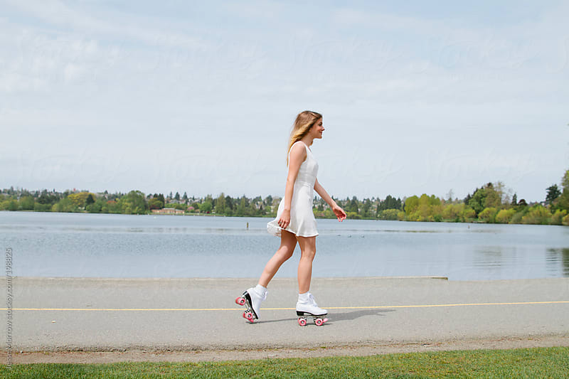 young woman roller skates around lake by Jesse Morrow for Stocksy United