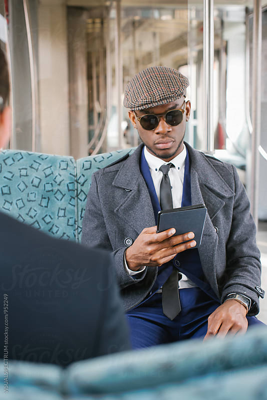 Stylish Young Black Businessman Reading Ebook on Commuter Train by Julien L. Balmer for Stocksy United