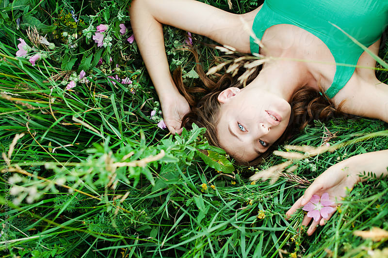 Young brunette girl lying down on grass by Sergey Filimonov for Stocksy United