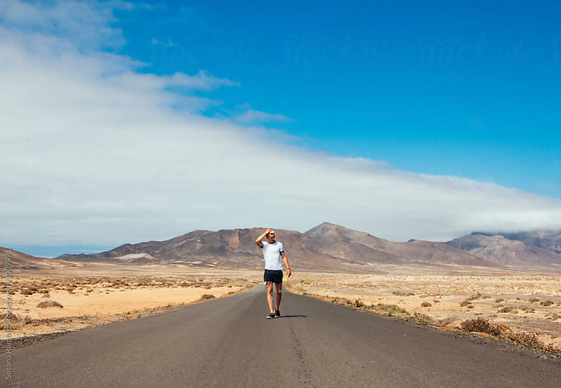 Young man walking down a long road with mountains in the background by Susana Ramírez for Stocksy United