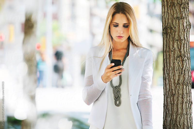 Young businesswoman working with smartphone on the street. by BONNINSTUDIO for Stocksy United