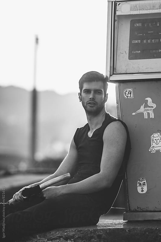 handsome man at a gas station at sunset by Igor Madjinca for Stocksy United
