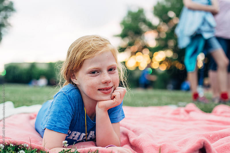 Smiling girl laying on a pink blanket in a park by Gabriel (Gabi) Bucataru for Stocksy United
