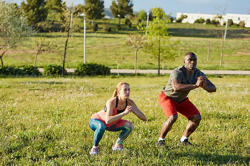 Determined Athletes Doing Squats On Grass In Park by ALTO IMAGES for Stocksy United