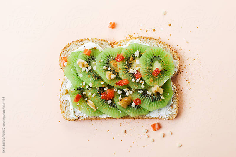 Kiwi, cream cheese, nuts and cinnamon on toast. by BONNINSTUDIO for Stocksy United