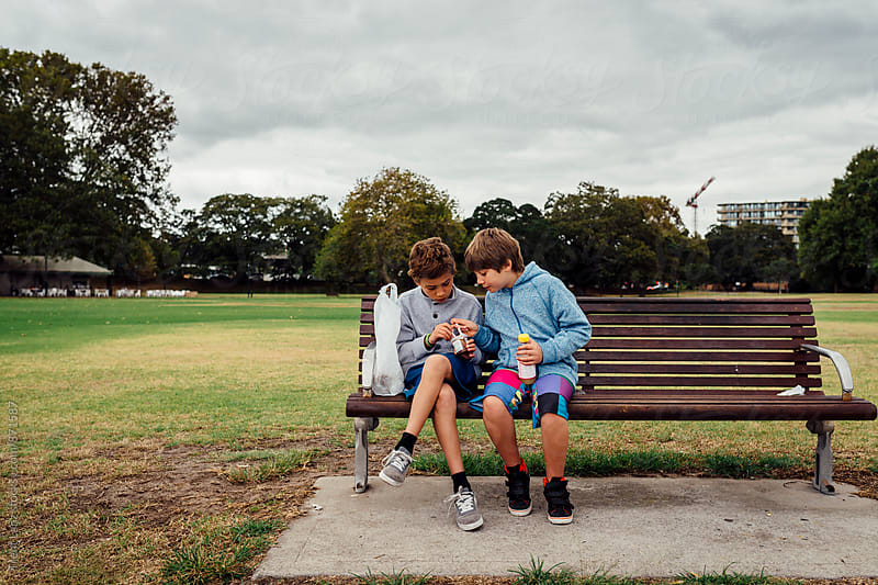 Two boys sitting on bench in park sharing food by Trent Lanz for Stocksy United