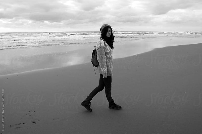Black and white - woman walking along the beach in winter by Lucas Ottone for Stocksy United