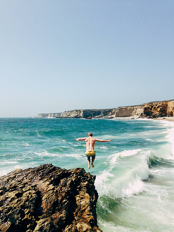 Man Jumping From A Rock Cliff Into The Ocean Waves With His Arms Stretched Out by Luke Mattson for Stocksy United