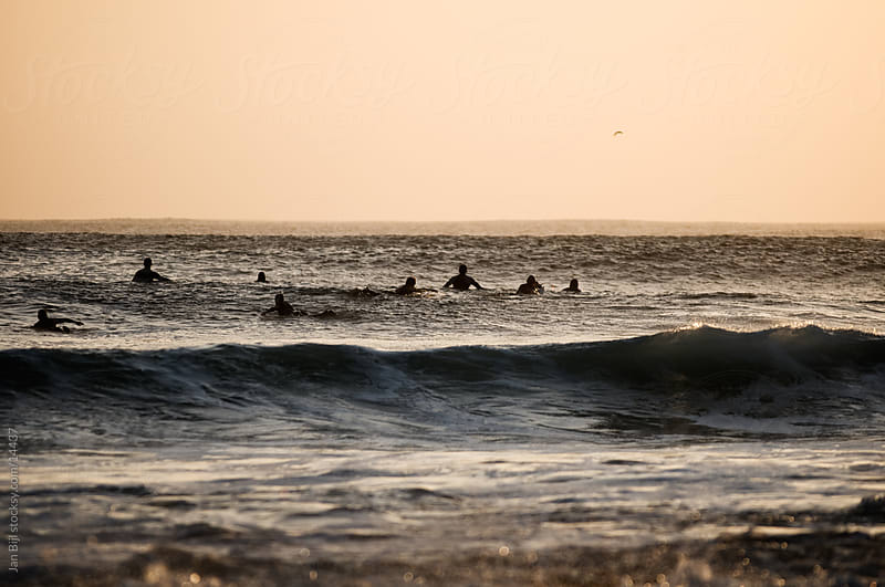 surfers waiting for waves, sunset session. by Jan Bijl for Stocksy United