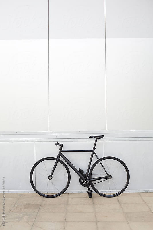 Bicycle parked in front of a silver grey wall by Miquel Llonch for Stocksy United