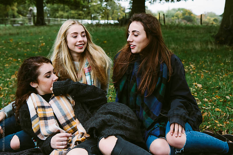 Three teenage girls outdoors, chatting. by Helen Rushbrook for Stocksy United