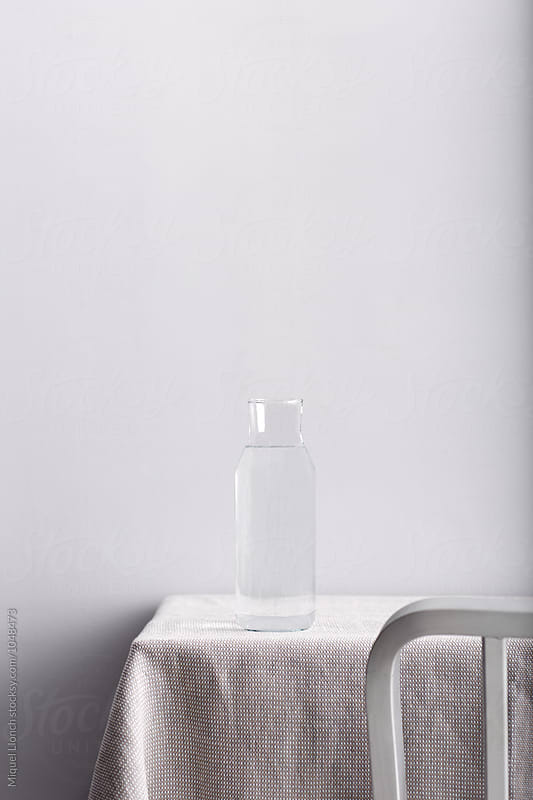 Tablecorner with a bottle of water and a chair by Miquel Llonch for Stocksy United