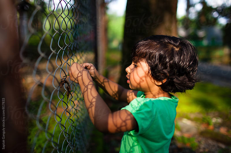 Little girl playing by the fence by Saptak Ganguly for Stocksy United