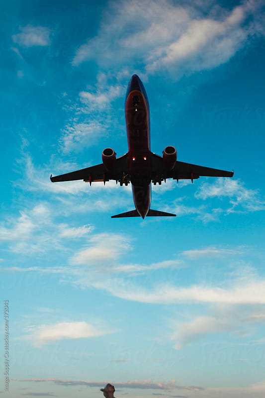 tiny head looking up at massive airplane in the sky by Image Supply Co for Stocksy United