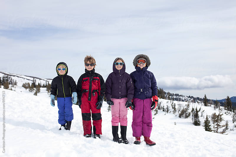 Four siblings in the snow on Mount Hood by Carleton Photography for Stocksy United