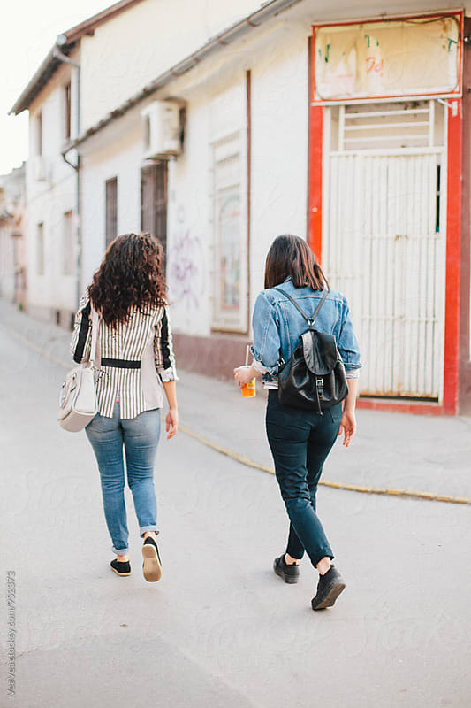 Two female friends walking down the street by VeaVea for Stocksy United