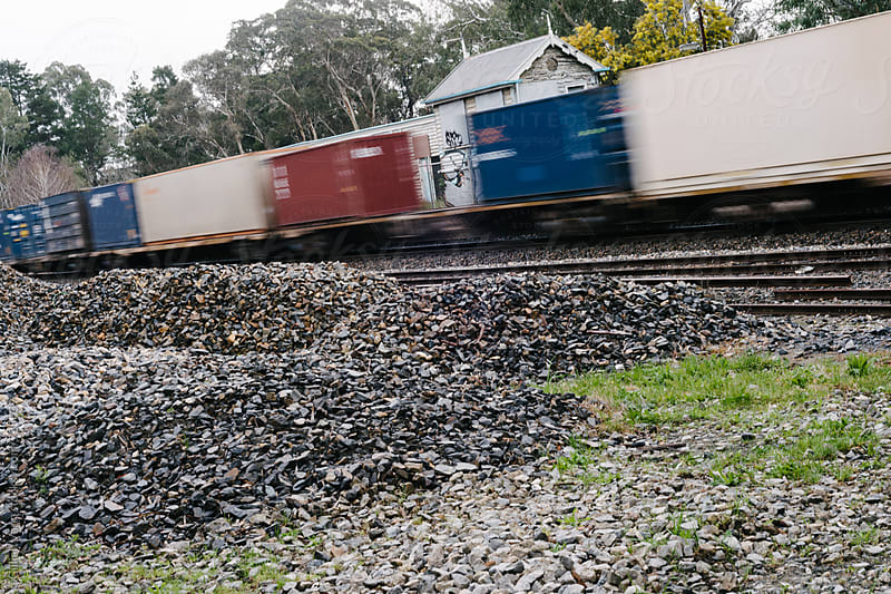 a freight train travels through an abandoned train station by Gillian Vann for Stocksy United