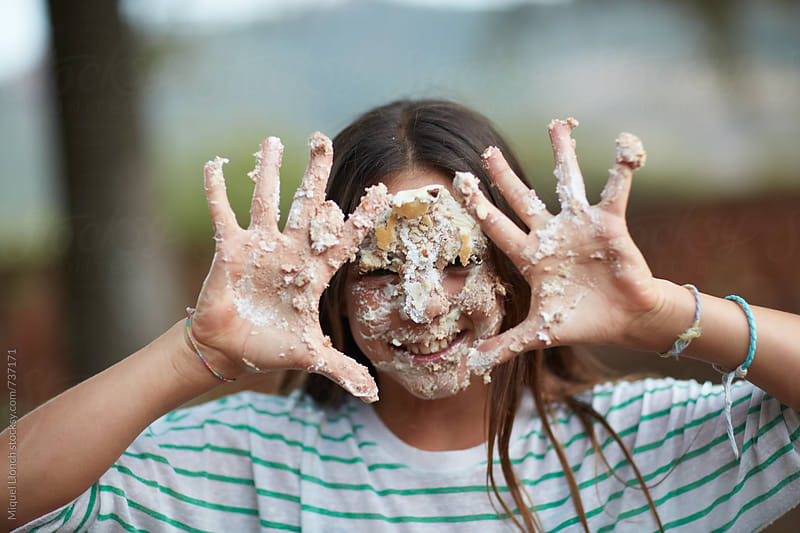 Young girl with dirty face and hands from a birthday cake by Miquel Llonch for Stocksy United