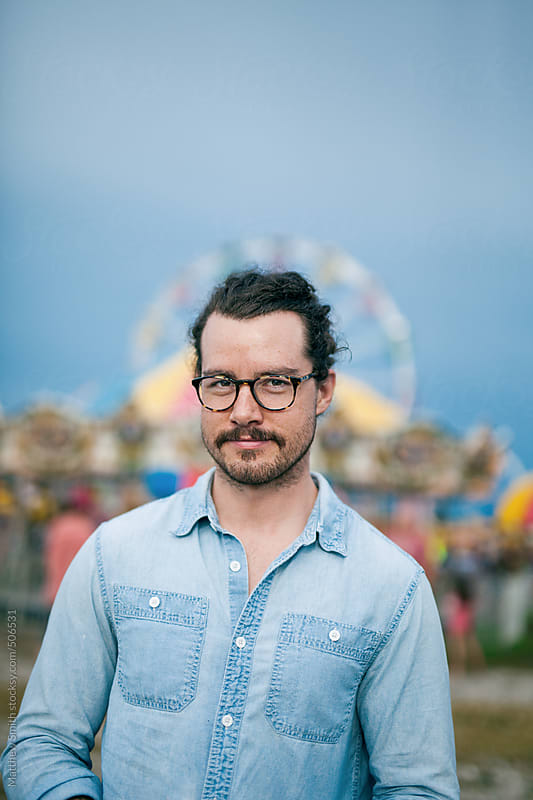 Attractive Man Stands In Front Of A Local County Fair by Matthew Smith for Stocksy United