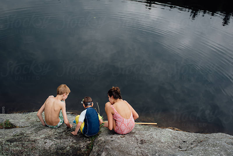 kids sitting by a lake with fishing net by Léa Jones for Stocksy United
