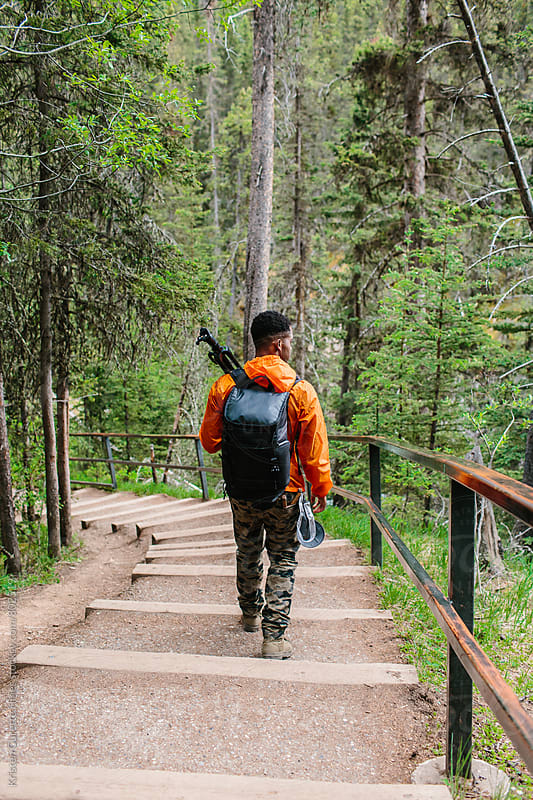A man walking down a stair case trail with his camera gear & tripod by Kristen Curette Hines for Stocksy United