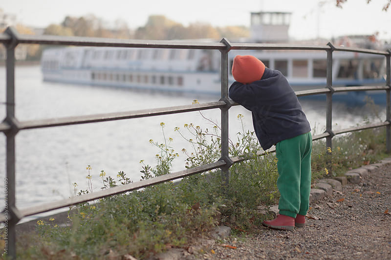 Toddler dreaming of a boat ride on a river by Mima Foto for Stocksy United