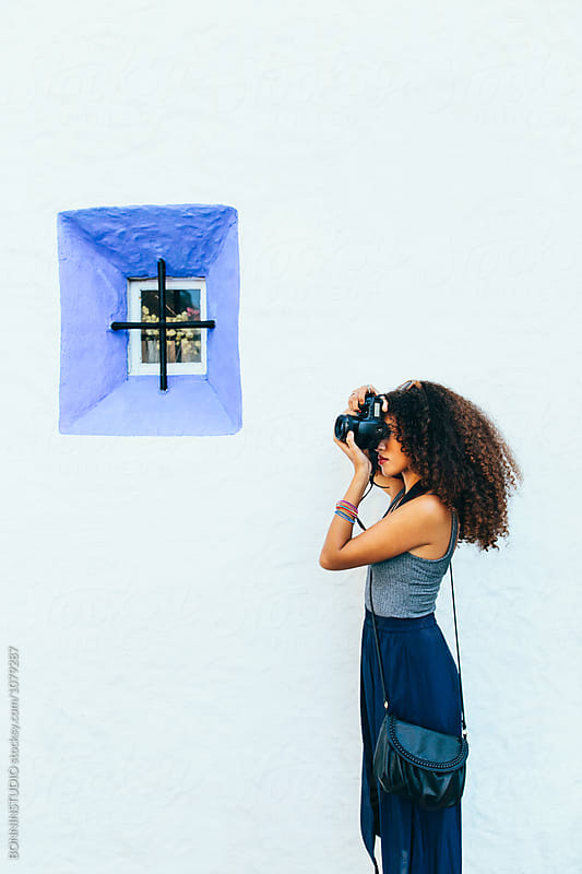 Side view of a chic tourist taking a photo with her camera.  by BONNINSTUDIO for Stocksy United