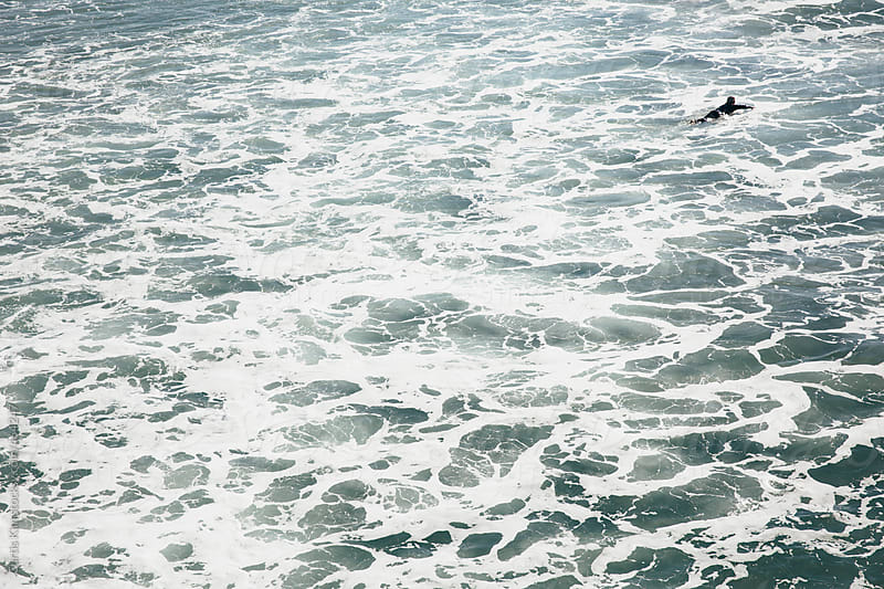 Surfer paddling in the midst of rough waters by Curtis Kim for Stocksy United