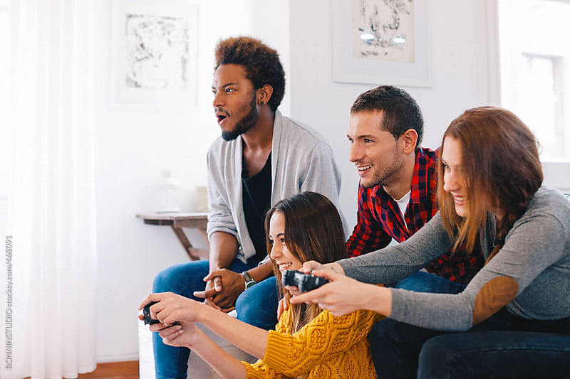 Group of happy young friends playing video games at home. by BONNINSTUDIO for Stocksy United