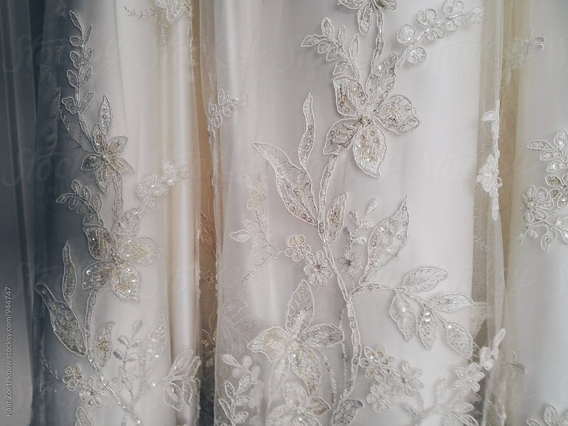 Close-up of lace and beading detail of an off-white wedding gown. by Kaat Zoetekouw for Stocksy United