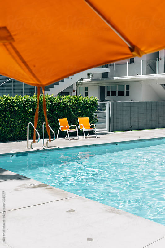 Two Orange Chairs At Edge Of Vacation Resort Swimming Pool by Luke Mattson for Stocksy United