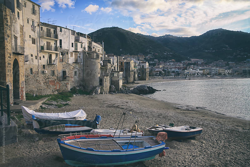 Boats on a sandy shore nearby old Sicilian houses by Alice Nerr for Stocksy United