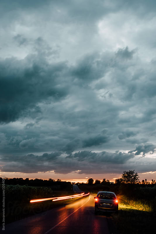 Dramatic sky with car on the road  by Boris Jovanovic for Stocksy United